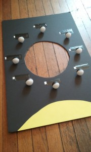 A rectangular black cardboard with a circle cut out of the center is shown. Black and white ping pong balls are taped at intervals around the circle representing the phases of the moon. A yellow half circle is taped to one end of the rectangle representing the sun.