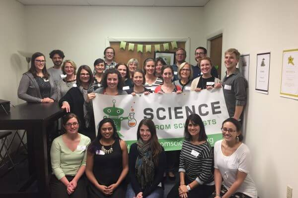 Massachusetts instructors holding a Science from Scientists banner at all staff training.