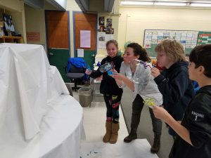 Scientist showing students how to use bubbles to showcase water against mountains.