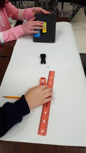 Students measuring distance with ruler.