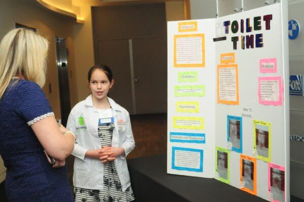 Adult listens to student describe Toilet Time experiment.