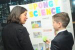 Adult speaks to student about Spongy Science experiment.