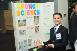 Student poses infront of Spongy Science experiment.