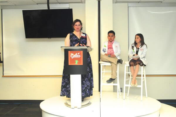 Teacher give a talk at Gala with two students behind her.