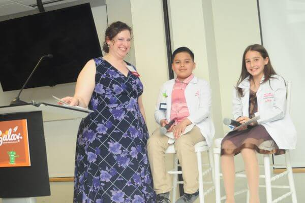 Teacher and two students on stage at Gala.