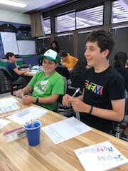 Two boys laugh while doing lesson.