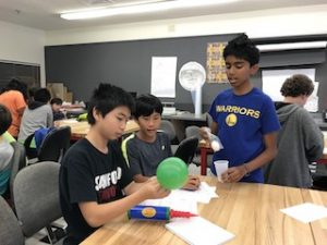 Three boys experimenting with balloons during forensic lesson.