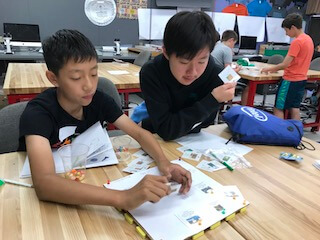 Two boys using picture cards to fill out chart.