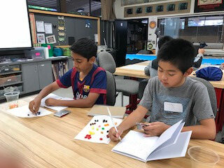 Two boys placing sorted beads on paper.