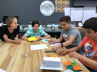 Teacher looks on as three boys sort beads.