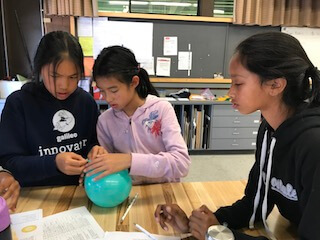 Three girls experimenting with balloon during forensic lesson.