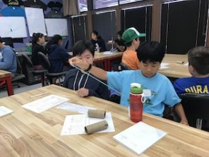 Two boys use string during science lesson.