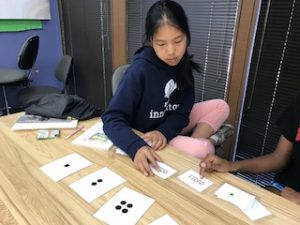 Girl uses observing flashcards to work through lesson.