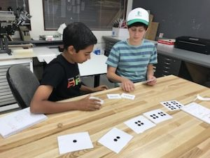 Two boys solving puzzle using flashcards.