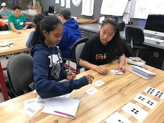 Two girls using flashcards during lesson.