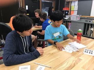 Two boys shuffling flashcards.