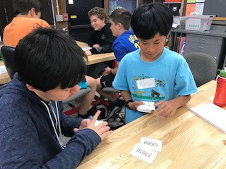 Two boys looking at flashcards.