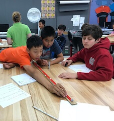 Three boys measuring distance with yardstick during forensic lesson.