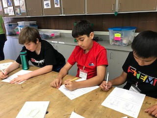 Three students sitting at a table all filling out their own worksheets.