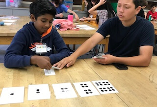 Two students using playing cards at a table with cards showing differing number of dots laying on the table in front of them.