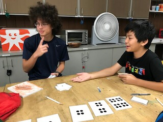Two students using large cards with dots to learn binary.