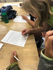 Students look at blood samples and fill in worksheets.