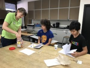 Scientist hands out jelly beans to two students sitting at a table.