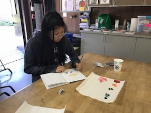 Student is sitting at a table writing in a notebook with different colored jelly beans on a papertowel next to her notebook.
