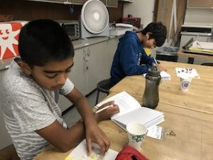 Two boys sitting at a table writing in their lab notebooks and looking at colored jelly beans.