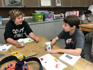Two students sitting at a table with different colored jelly beans in front of them on the table, each holding their own cup.