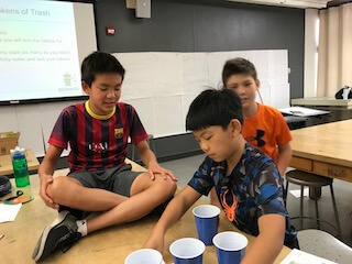One student sitting on a table, as another organizes cups into a pattern and a third student looks on in the back.