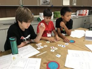 Three students working at a table with small cards, worksheets and paper decoder wheels.