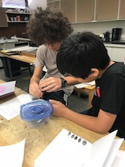 Two students working at a table.