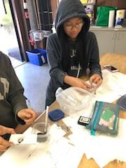 Students dusting for fingerprints on a tile.