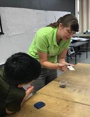 Scientist demonstrating for student how to dust a tile for fingerprints.
