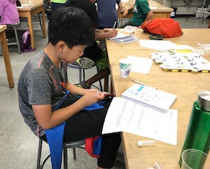 One student sitting at a table with a notebook and worksheet in front of him.