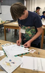 Student standing at a table arranging small cards into a food web.