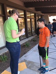 Scientist explaining an activity to a student while standing outside.