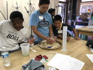 Three students molding sand for planet Earth.