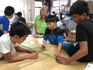 Instructor looks on as three students measure planetary distance with legos.