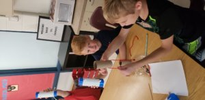 Two boys are creating model mystery tubes. One is holding a pvc pipe, the other is holding a cardboard tube and yarn.