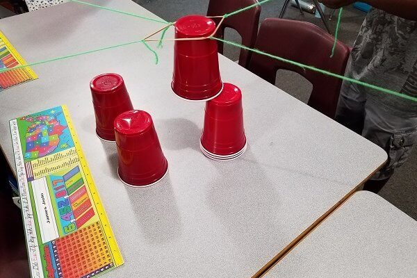 A table with 4 solo cups is shown. One cup has strings attached.