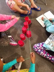 Students work as a team with strings to try to lift a solo cup off the floor.