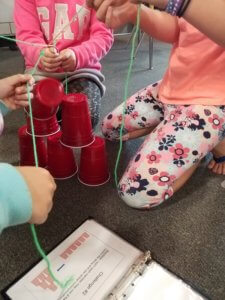 Students work to build a solo cup pyramid using strings to move the cups.