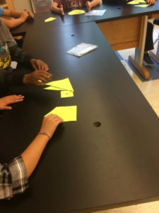 Student hands are shown putting shapes together in a puzzle.