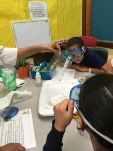 Students wearing goggles watch a thermometer in a plastic bag.
