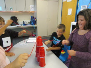 Students pull on strings attached to solo cups to stack them in a tower.