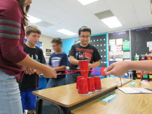 Students pull on strings attached to solo cups to stack them.