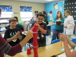 Students pull on strings attached to solo cups to stack them in a tower as teacher and scientist watch.
