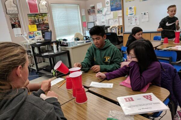 Students sitting at a table use strings to stack solo cups on top on one another.